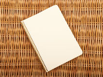 Beautiful background. Notebook on  natural basket textures background Stock Photos