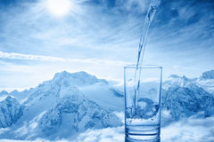 Beautiful background of pouring blue water in transparent glass. Over winter landscape of mountains higher than clouds, close up Royalty Free Stock Images