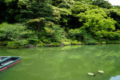 Beautiful background scene of lush green japanese garden mountain landscape with shades of green plant, boat, lotus pond, etc. Stock Photos