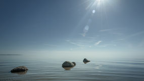Beautiful background stones in clear blue water against the sky Royalty Free Stock Photography