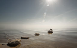 Beautiful background stones in clear blue water against the sky Royalty Free Stock Images