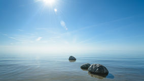 Beautiful background stones in clear blue water against the sky Stock Image