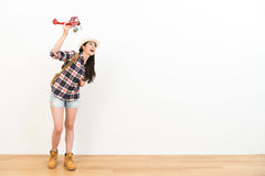 Beautiful backpacker lady standing on wooden floor. Happy beautiful backpacker lady standing on wooden floor with white wall background and holding retro Stock Photo