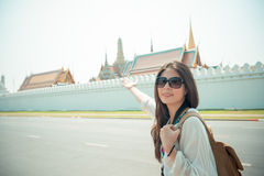 Beautiful backpacker showing famous location. Attractive beautiful backpacker showing famous travel location and showing awesome Grand Palace behind her. Happy Stock Photography