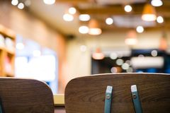 Beautiful backrest brown chair for meeting at coffee shop and fast food blurry bokeh background.wooden chair for sitting and. Eating meal at beautiful stock photo