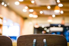 Beautiful backrest brown chair for meeting at coffee shop and fast food blurry bokeh background.wooden chair for sitting and. Eating meal at beautiful stock photos