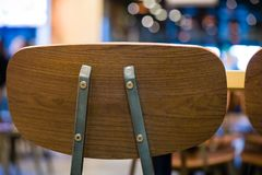 Beautiful backrest brown chair for meeting at coffee shop and fast food blurry bokeh background.wooden chair for sitting and. Eating meal at beautiful royalty free stock photo