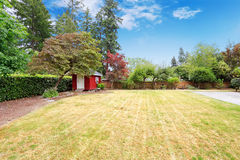 Beautiful backyard with small red shed Royalty Free Stock Image