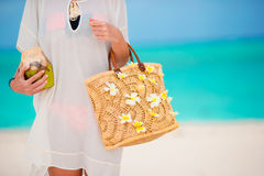 Beautiful bag with frangipani flowers and cocnut in female hands. Beach accessories - adorable bag with frangipani flowers and sunglasses on white beach Stock Photo