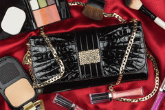 Beautiful bag from patent leather and cosmetics lying on red sat Royalty Free Stock Images