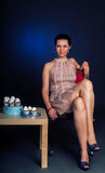 Beautiful baker resting on a chair. Pretty woman baker resting with crossed legs near table with cupcakes royalty free stock photo