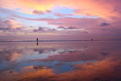 Beautiful Balinese sunset at Kuta beach with peoples and sky reflection in sand Royalty Free Stock Photography