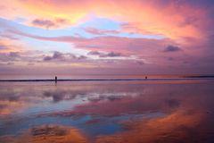 Beautiful Balinese sunset at Kuta beach with peoples and sky reflection in sand Stock Photography