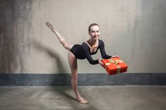 Beautiful ballerina balance in one leg and holding red gift box royalty free stock photo