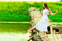 Beautiful ballerina balancing on the bridge by the river Stock Photos