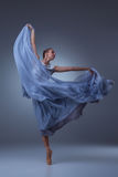 The beautiful ballerina dancing in blue long dress Stock Photography