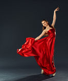 Beautiful ballerina dancing a long red dress flying Stock Photo