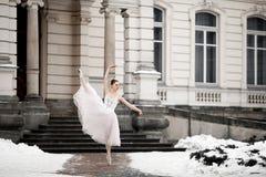 Beautiful ballerina dancing next to building on snow background stock photos