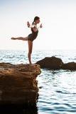 Beautiful ballerina dancing, posing on rock at beach, sea background. royalty free stock images