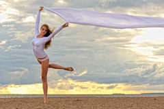 Beautiful ballerina dancing at the sea beach. Stock Photos