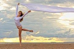 Beautiful ballerina dancing at the sea beach. stock photos