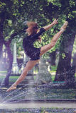 Beautiful ballerina girl in casual clothes posing on a blurred background of the park trees on background feet closeup royalty free stock images