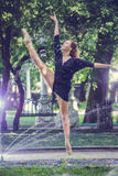 Beautiful ballerina girl in casual clothes posing on a blurred background of the park trees on background. Beautiful ballerina girl in casual clothes posing on stock images