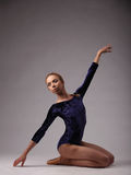 Beautiful ballerina with perfect body in blue outfit on gray studio background. on her knees, one hand up Stock Image