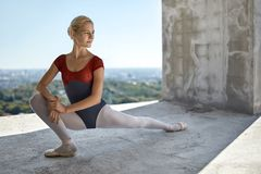 Ballerina posing at unfinished building. Beautiful ballerina is posing on the concrete floor of the unfinished building on the cityscape background. She wears a Stock Photo