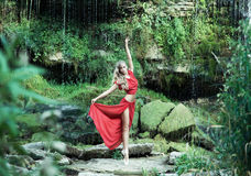 A beautiful ballerina in a red dress dancing in the forest Royalty Free Stock Photos