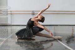 Beautiful ballerina sit on the twine in class Stock Image