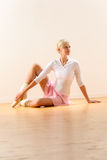 Beautiful ballerina sitting on floor holding ankle Royalty Free Stock Photo