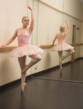 Beautiful ballerina standing en pointe with the barre Stock Images