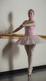 Beautiful ballerina standing en pointe holding barre Royalty Free Stock Photography