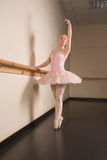 Beautiful ballerina standing en pointe holding barre Royalty Free Stock Images
