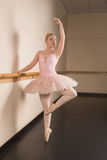 Beautiful ballerina standing en pointe holding barre Stock Photography