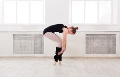 Beautiful ballerina stands in ballet assemble. Young graceful ballerina in black at ballet class making assemble. Classical dancer in white hall practicing stock photography