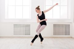 Beautiful ballerina stands in ballet assemble. Young graceful ballerina in black at ballet class making assemble. Classical dancer in white hall practicing royalty free stock images