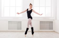 Beautiful ballerina stands in ballet assemble. Young graceful ballerina in black at ballet class making assemble. Classical dancer in white hall practicing royalty free stock photos