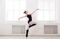 Beautiful ballerina stands in ballet pirouette. Young graceful ballerina in black at ballet class making pirouette. Classical dancer in white hall practicing Royalty Free Stock Images