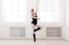 Beautiful ballerina stands in ballet pirouette. Young graceful ballerina in black at ballet class making pirouette. Classical dancer in white hall practicing Stock Photos
