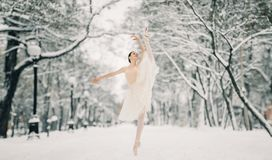 Beautiful ballerina is dancing at walkway of snowy city royalty free stock image