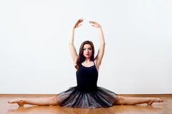 Beautiful ballerina in tutu performing split on the floor Stock Photography