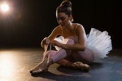 Ballerina tying her shoes. Beautiful ballerina tying her shoes royalty free stock image