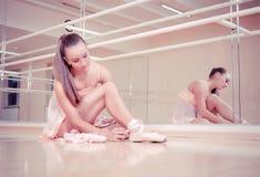 Beautiful ballerina tying shoes stock image