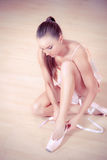 Beautiful ballerina tying shoes Stock Photography