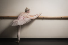 Beautiful ballerina warming up with the barre Stock Image
