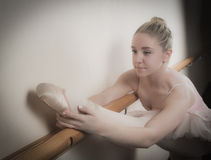 Beautiful ballerina warming up with the barre Stock Photo