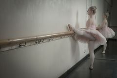 Beautiful ballerina warming up with the barre Royalty Free Stock Photography