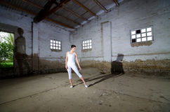 Beautiful ballerina in white dancing in abandoned building Royalty Free Stock Images